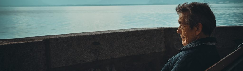 Elderly man sitting on bench looking out at the sea
