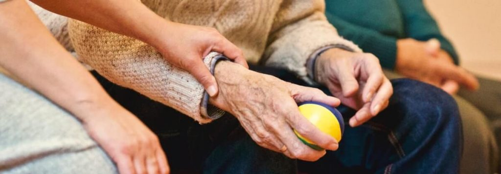 Nursing Home Staff Holding older persons hand while the older man holds a stress ball.