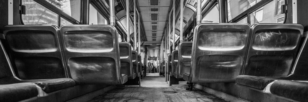 empty aisle of a mass transit vehicle (bus) in black and white