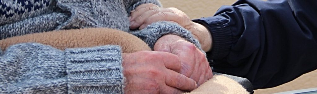 Quality Nursing Home Staff Member holding hands with elderly person.