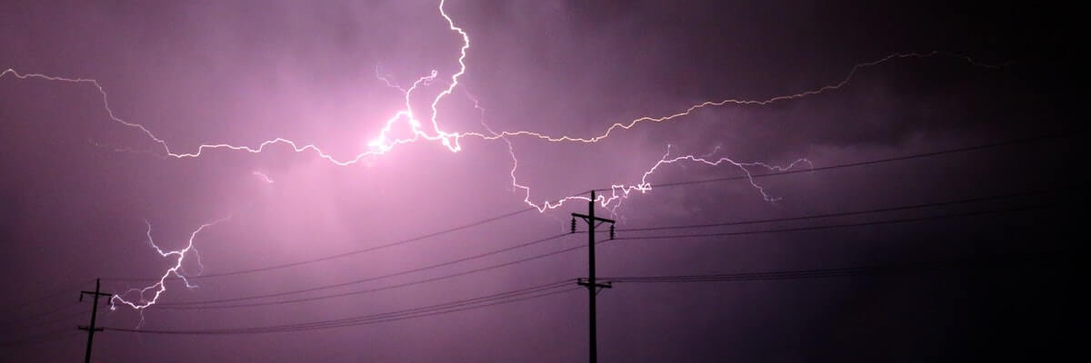Lightning flashing against a backdrop of purple sky and electricity poles