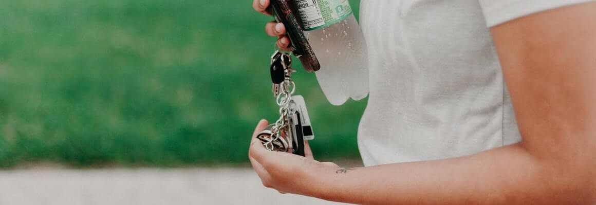 woman wearing white tshirt holding leased car keys, her phone, and a bottle of water. Set against a grass field.