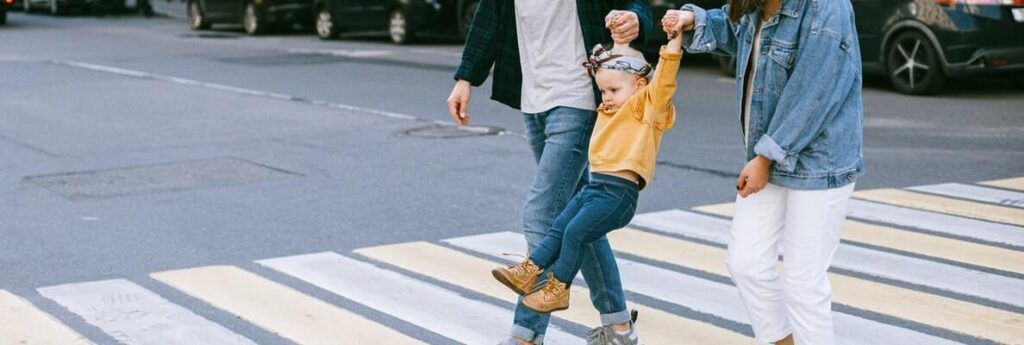 parents with daughter crossing the street
